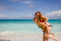 Picture of a teenage girl giving her mother a piggback ride on a hawaiian beach with tropical blue green waters beckoning behind. Great vacation photos for travel.