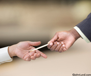 An African American Executive's hand holds a pen out to another man's hand ready to sign the documents to seal the deal. Advertising photogrpahy for small business or big business. Ad pics.
