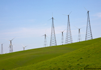 Wind turbines on a green, grassy hillside. Wind power, renewable energy, wind farm. Towering windmills producing electricity on a rolling green hillside against a clear blue sky.