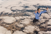An Asian American business man is flying high above a city seen below the clouds in a photo of success and super powers.