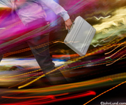 Picture of a rushing executive, briefcase in hand, speeding ahead through a splash of colorful streaking lights for use in business ads.