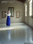 Woman doing aikido with a sword. The woman is an Aikido Sensei, a teacher, in a Dojo or martial arts studio. The sword is made of wood.