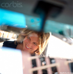 Photo of a womans reflection in her rear view mirror as she drives her car. The woman is blonde and is smiling.