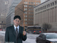 A businessman looks gloomily towards the camera while he holds up an umbrella with no fabric left to protect him from rain.