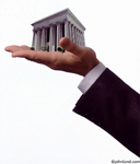 Picture of a bank building in the palm of a mans hand. This big banking photo can illustrate finanical services or corruption and insider trading. Too big to fail.