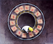 Circular conveyor belt and a worker wearing a yellow hard hat. Packages are speeding around in an endless circle.  A  photo about inefficiency and waste.