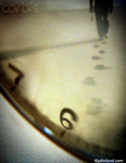 Picture of Footprints Reflected in a Watch. Close up cropped watch face showing footsteps on the face and in the distance a man walking away from the camera.