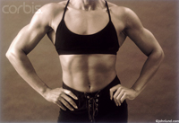 Muscular woman, hands on her hips, abdominals showing as she stands in a positon of strength, authority and power. An attractive female bodybuilder.