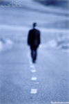 Picture of a man walking alone down a desolate and empty road in an image about isolation, solitude and loneliness.