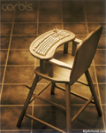 Highchair with a keyboard. Picture of computing at a young age and introducing computing to children. Sepia colored image of an old fashioned wooden baby's high chair but with a keyboard built into the tray.