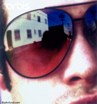 Man wearing sunglasses. Serious contemporary man, close-up shot. Cropped tight, this swarthy, sexy, man has a reflection of a building showing in the lens of his dark sunglasses.