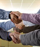 Three pairs of hands reach across each other in handshakes in an office setting showing teamwork and cooperation. Picture of many hands shaking.