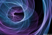An abstract light pattern of blue and purple light trails swirl around illustrating motion, energy and cyberspace.