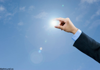 A hand reaches out as if to grasp the sun in this concept stock picture about alternative energy and solar power for advertising and editorial use. Green energy and renewable energy pictures for advertising.