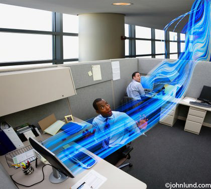 Information is streaming in and out of computers in an office as business people look on in awe and surprise. The information is visualized as blue streaks of light flowing from computer monitors.