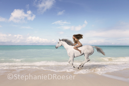 A nude woman, long hair blowing behind her, races across a beach astride a white horse in a concept stock photo about freedom, adventure and fantasy.