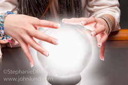 A fortune teller's hands hover over a glowing crystal ball as she looks into the future for premonitions.