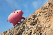 Sweat equity: A piggy bank breaks out in beads of sweat as he climbs a steep hill in a photo about sweat equity, investment and finance.