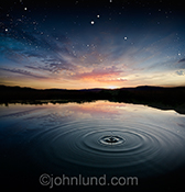 A single drop of water sends out ripples over a lake at sunset in a stunningly beautiful stock photo about purity, nature and repercussions.