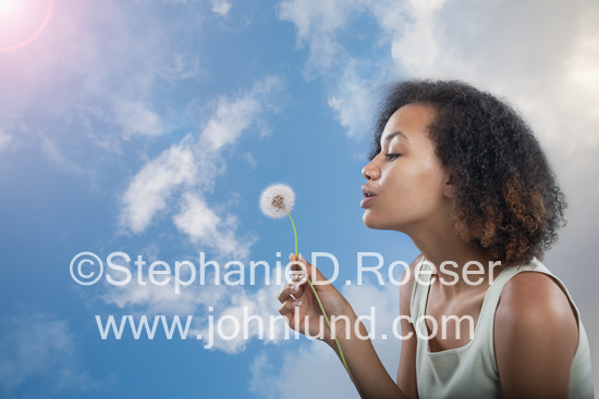 Picture of a young African American woman blowing Dandelion seeds on a bright spring morning and making wishes to be carried by the wind to thier ultimate fulfillment.