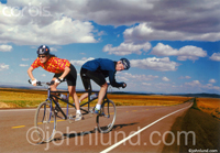 A man and a woman cycling in opposite directions on a bicycle built for two. This image is about team work and relationships. The couple is on a long strait road leading off to the horizon. The blue sky is rife with fluffy clouds.