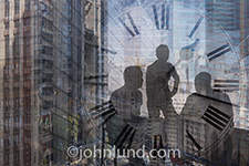 Three business people meet in a high rise office with a clock face superimposed over the image in a reference to time issues and deadlines.