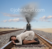 A businesswoman has her ear to the railroad tracks listening for an oncoming train, oblivious to the steam locomotive quickly approaching; A stock photo about awareness.