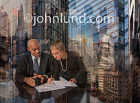Sealing the deal, teamwork, and global partnerships are concepts illustrated by this photo of a male and female executive signing a document in an intricate urban setting.