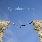 Picture of a human bridge of businessmen spanning a gap between two cliffs and demonstrating the concept of teamwork.