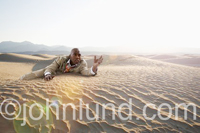 An African American man, in a tattered business suit, crawls through the dessert. crawling through the desert pic.