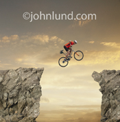A mountain biker is frozen in mid-flight as he attempts to jump on his bike from one cliff edge to another as the sun sets behind him.