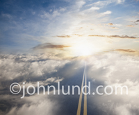 A picture of the road to cloud computing showing a long road leading over and through the clouds culminating in a beautiful sunrise.