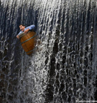 A businessman is seen plunging over a waterfall in a barrel in a concept stock photo about risk, adversity and adventure. Picture of  a crazy stunt.