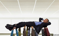 An Asian American businessman lays back as he is lifted into the air by his support staff in an office environment.
