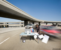 A businessman and business woman are working at a desk in the middle of a busy freeway. Cars are zipping by at high speed, causing the woman's hair to blow and papers to fly off of the desk.